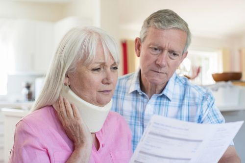 Mature Couple Reading Letter About Wife's Injury - Hampton & Royce, L.C.
