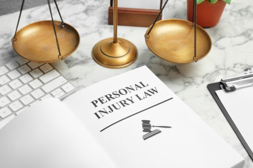 Personal injury law book and scales of justice on the table