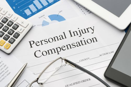Personal injury form on a desk with a calculator, pen, glasses, mobile phone and digital tablet. - Hampton & Royce, L.C.